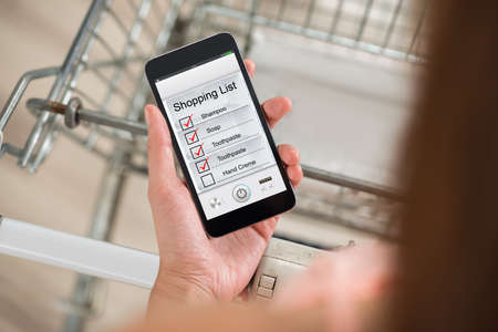 carretilla de mano: Vista de ángulo alto de la mujer con la lista de la compra de cheques carretilla de mano en el teléfono inteligente en el supermercado