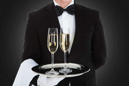 alcohol server: Midsection of waiter carrying champagne flutes on tray over gray background