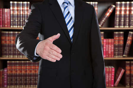 account executive: Midsection of attorney offering handshake against books in shelves