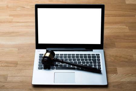 orden judicial: Vista de ángulo alto de la computadora portátil y un mazo sobre la mesa en juzgado