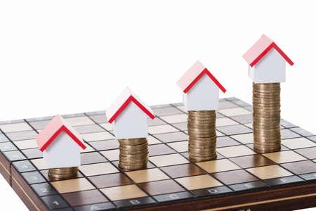 집 모델 및 흰색 배경에 체스 판에 누적 된 동전 스톡 콘텐츠