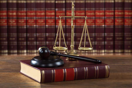 Closeup of mallet and legal book with justice scale on table in courtroom 스톡 콘텐츠