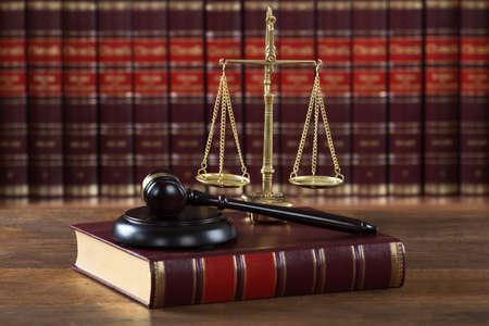 Zbliżenie z młotka i książki prawnej ze skalą sprawiedliwości na stole w sali sądowej