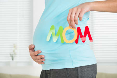 midsection: Midsection of pregnant woman holding word mom while touching stomach at home Stock Photo