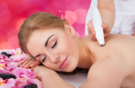 spa therapy: Relaxed young woman receiving microdermabrasion therapy at beauty spa Stock Photo