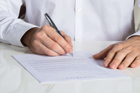 certify: Midsection of businessman signing contract document at office desk Stock Photo