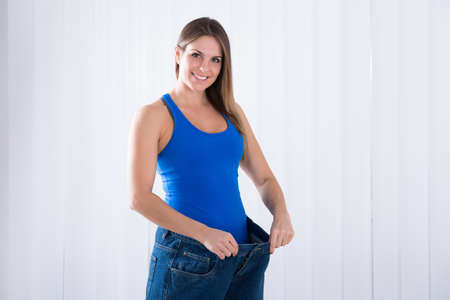 weightloss: Happy Young Woman Showing Her Weightloss By Wearing Old Jeans