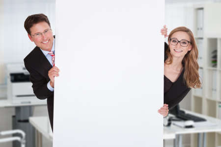 Portrait of male and female business people hiding behind blank billboard in office