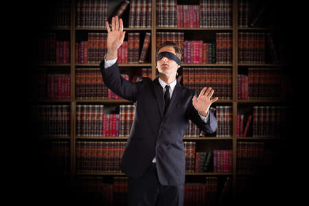 ojos vendados: Con los ojos vendados joven abogado haciendo un gesto de pie sobre los estantes de libros en la oficina