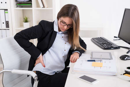 backpain: Young Businesswoman With Backpain Sitting On Chair At Workplace