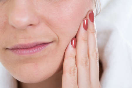 touching face: Close-up Of A Woman With Toothache Touching Face Stock Photo