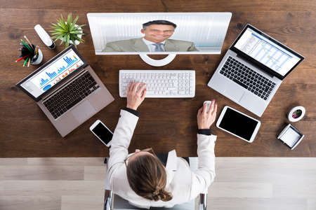 elearning: Businesswoman Videoconferencing With Senior Colleague On Desktop Computer