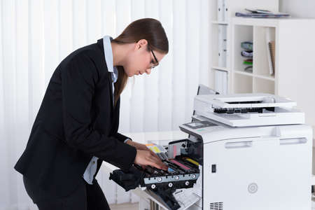 photocopier: Young Businesswoman Fixing Copy Machine At Workplace