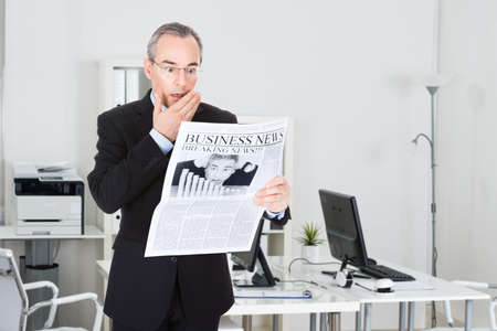 traumatized: Shocked mature businessman reading newspaper while standing in office