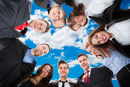 directly below: Directly below portrait of diverse business team forming huddle against sky