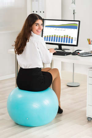 Portrait of happy young businesswoman using computer while sitting on exercise ball in office Stock Photo