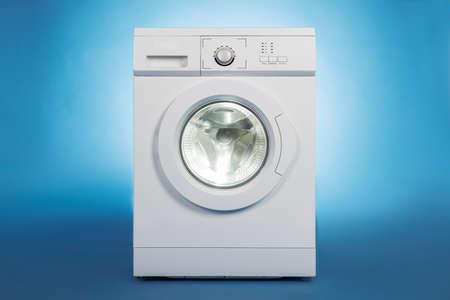 a machine: White washing machine isolated over blue background
