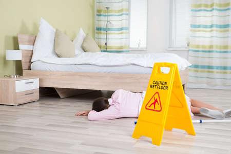 orden y limpieza: Señal de sexo femenino joven ama de casa inconsciente cerca de Piso mojado En La Habitación