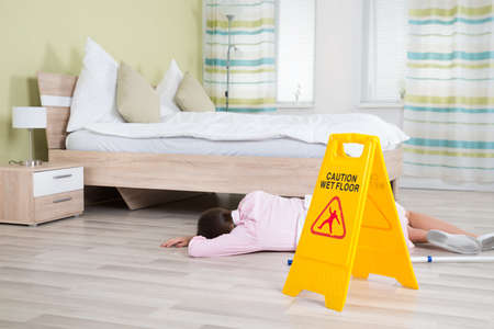 the unconscious: Young Female Housekeeper Unconscious Near Wet Floor Sign In Hotel Room Stock Photo