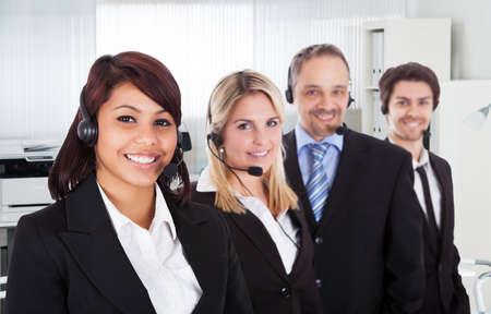 representatives: Portrait of confident call center representatives smiling in office Stock Photo