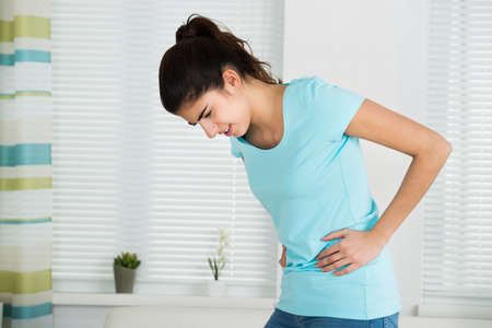 Young woman suffering from stomach ache standing at home Stock fotó