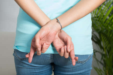 hope indoors luck: Rear view midsection of woman with fingers crossed at home