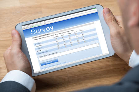 online survey: Cropped image of businessman giving online survey on digital tablet at office desk Stock Photo
