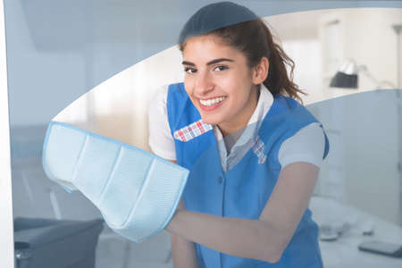 house maid: Portrait of happy young female worker cleaning glass window with rag at office Stock Photo