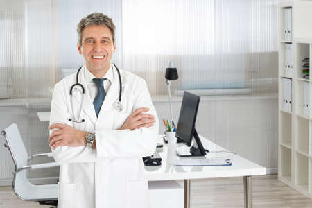Portrait of confident male doctor standing arms crossed in clinic photo