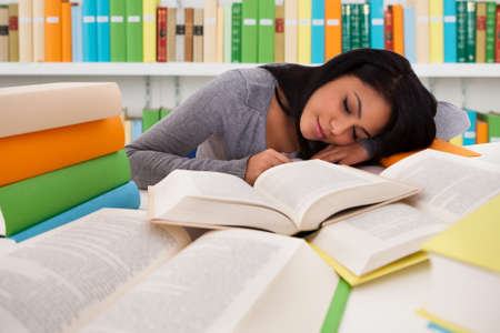Tired female university student sleeping on books at desk in library