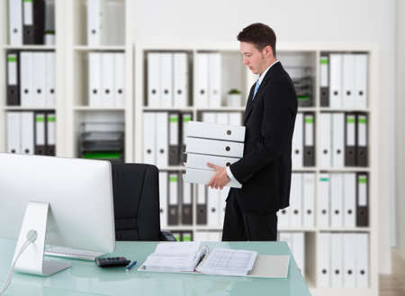 working desk: Side view of young businessman carrying binders by desk in office