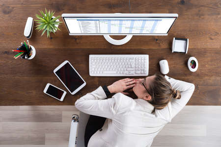 broken chair: Young Businesswoman Sleeping In Front Of Computer At Desk