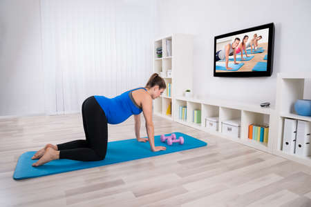 Healthy Pregnant Woman Exercising In Front Of Television In Living Room photo