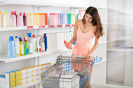woman shopping cart: Smiling young woman with shopping cart buying beauty product in supermarket
