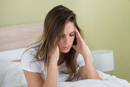 dolor de cabeza: Retrato de una mujer joven con dolor de cabeza que se sienta en cama