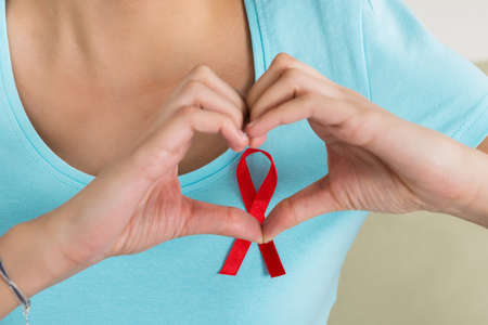 medical fight: Young woman making heart shape in front of AIDS awareness ribbon at home