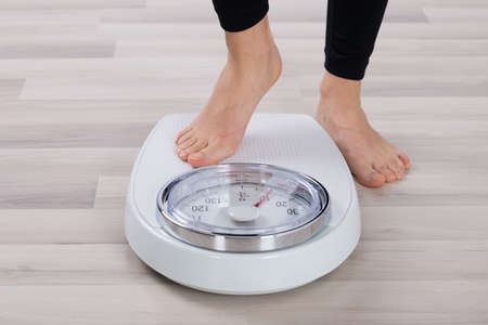 low scale: Low Section Of Person Standing On Weighing Scale