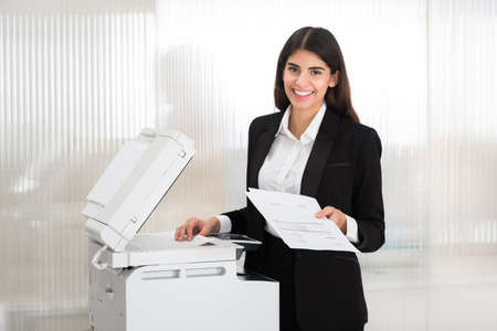 fax: Young businesswoman using photocopy machine in office
