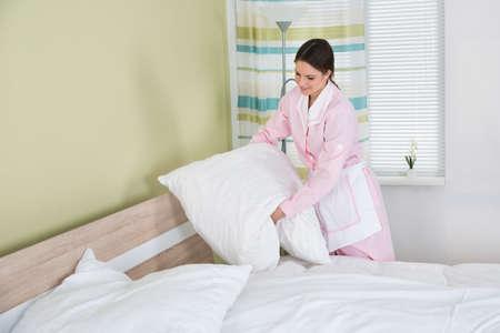 orden y limpieza: Mujer feliz ama de casa Organizar blanco almohadas en la cama en la habitaci�n