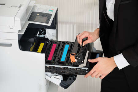 Midsection of young businessman fixing cartridge in printer machine at office Zdjęcie Seryjne - 51726275