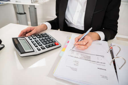 High angle view of young businesswoman doing financial calculation at desk in office Stock Photo
