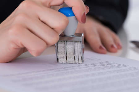 form: Close-up Of Businessperson Hand Using Stamper On Document Stock Photo