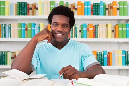 sitting at desk: Portrait of happy male student sitting at desk in library