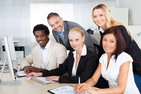Portrait of multiethnic business people working at desk in office photo