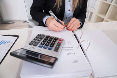 account executive: Close-up Of A Businesswoman Calculating Invoice With Calculator