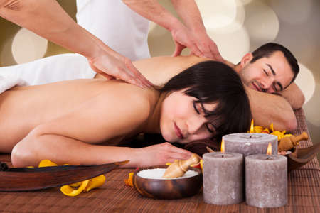 massage homme: Calme jeune couple qui reçoit le massage du dos au spa beauté Banque d'images