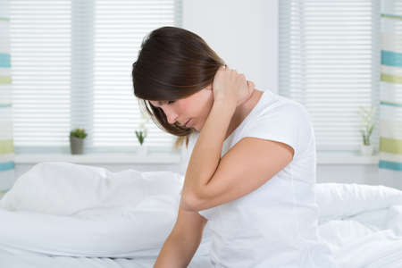 woman in bed: Young Woman Suffering From Neck Pain Sitting On Bed Stock Photo