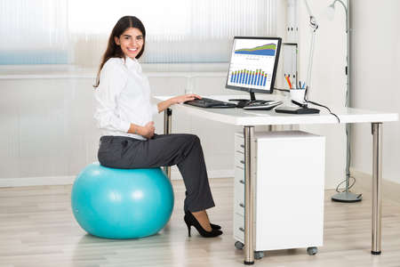 Seitenansicht der schwangeren Geschäftsfrau Computer, während im Büro sitzt auf Ausübung Ball