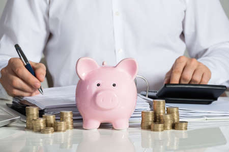 midsection: Midsection of businessman calculating invoice with piggybank and coins at office desk Stock Photo