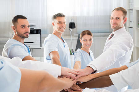 joining hands: Portrait of confident medical team smiling while joining hands in clinic Stock Photo